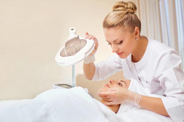 Frau liegt unter einer Lampe in Kosmetikbehandlung